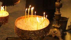 Brandende kaarsen binnen van orthodoxe kerk, betalend eerbied, godsdienstige traditie stock videobeelden