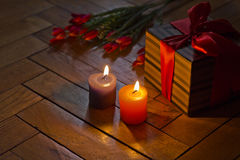 Brandende kaarsen, de open huidige, rode tulpen van de giftdoos op houten bac Royalty-vrije Stock Afbeelding