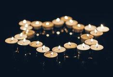 Brandende kaarsen in de vorm van een ster van David op een zwarte achtergrond Bokeh op donkere achtergrond, ondiepe diepte van ge Royalty-vrije Stock Foto