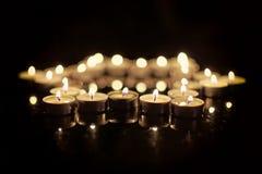 Brandende kaarsen in de vorm van een ster van David op een zwarte achtergrond Bokeh op donkere achtergrond, ondiepe diepte van ge Stock Afbeeldingen