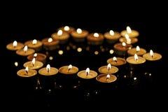 Brandende kaarsen in de vorm van een ster van David op een zwarte achtergrond Bokeh op donkere achtergrond, ondiepe diepte van ge Stock Foto