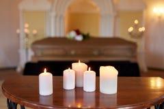 Brandende kaarsen en doodskist in kerk bij begrafenis stock foto's