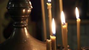 Brandende Kaarsen in Kerk, mensen gezette kaarsen stock videobeelden