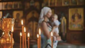 Brandende kaarsen in kerk, moeder met baby op vage achtergrond stock footage