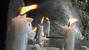 Brandende kaarsen op een steengebied stock footage