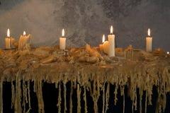 Brandende kaarsen op gesmolten was Vele brandende kaarsen Vele brandende kaarsen Stock Afbeeldingen