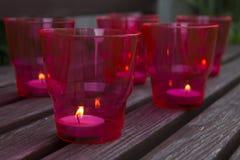 Brandende kaarsen in rode plastic glazen op uitstekende houten achtergrond Selectieve nadruk stock afbeelding