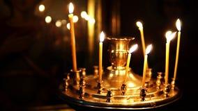 Brandende kaarsen voor de Orthodoxe pictogram langzame motie stock footage