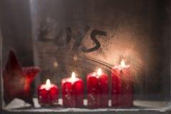 Brandende komstkaarsen op het berijpte venster met 2015 nieuwe year Stock Afbeeldingen
