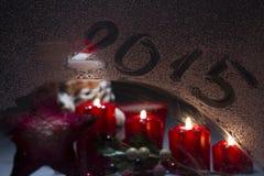 Brandende komstkaarsen op het berijpte venster met 2015 nieuwe year Royalty-vrije Stock Foto