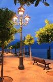 Brandende lantaarn bij de oever van het meerpromenade Stock Foto's