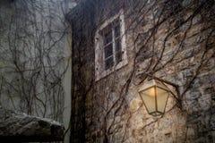 Brandende lantaarn op de muur van de oude stad stock foto