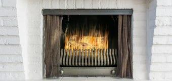 Brandende open haard met ijzergordijnen op de achtergrond van de close-upwinter royalty-vrije stock afbeeldingen