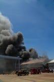 Brandende pakhuizen met zwarte rook tegen blauwe hemel Stock Foto