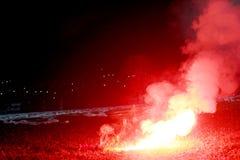 Brandende rode gloed, vlam, voetbalhooligan de voetbalventilators staken omhoog de lichten en de rookbommen op de voetbalhoogte a stock afbeelding