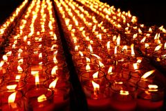 Brandende rode kaarsen Kaarsen lichte achtergrond Kaarsvlam bij nacht Stock Afbeelding