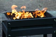Brandende steenkolen en vlam in koperslager op picknick royalty-vrije stock afbeelding