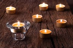 Brandende theekaarsen op de achtergrond van oude houten planken stock foto's