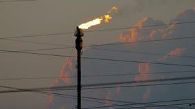 Brandende toorts bij de raffinaderij tegen de bewolkte hemel stock footage