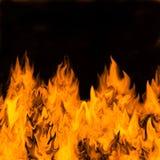 Brandende vlammen tegen dark Royalty-vrije Stock Foto's