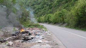 Brandende wilde huisvuilstortplaats Plastic zakken, flessen, afval en vuilnis dichtbij rivier Zwaar vervuilde rivierbank Milieupo stock footage