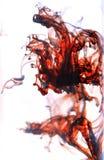 Brandfärg av målarfärg plaskar i vatten på vit Arkivfoto