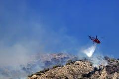 Brandhelikoptern släcker branden på backen Grekland Arkivfoto