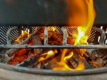Brandhout het branden in een brand die een barbecue opwarmen stock foto's