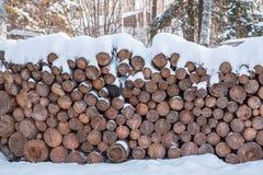 Brandhout in stapels wordt, met sneeuw worden behandeld gestapeld die cutted boomstammen in een alpiene hut in de winterbos stock foto
