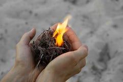Brandhoutvuller in handen met matchstick, zandachtergrond stock fotografie