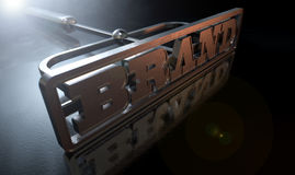 Branding Brand Concept. A metal cattle brand with the word brand as the marking area on an isolated dark backlit surface and background stock photos