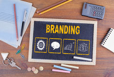 Branding concept. Chalkboard on wooden office desk royalty free stock photos