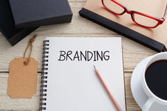 Branding concept. With notebook, brand tag and product box and coffee on work desk Stock Image