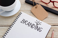 Branding idea. Concept with notebook and brand tag and coffee on work desk Royalty Free Stock Image