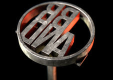 Branding Iron Brand. A metal cattle branding iron with the word brand as the marking area on an isolated dark surface - 3D render Stock Images