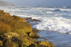 Branding langs rotsachtige kustlijn Stock Afbeeldingen