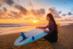 Brandingsmeisje en oceaan Het mooie jonge meisje van de vrouwensurfer met surfplank op een strand bij zonsondergang of zonsopgang Stock Foto