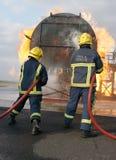 Brandkämpar som slåss brand Arkivbild