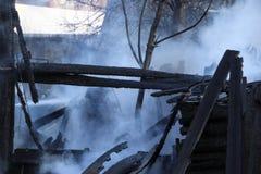 brandkatastrof fördärvar och återstår av ett bränt trähus Bränt bränt till kol vedträ i tjock rök royaltyfri bild