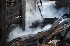 brandkatastrof fördärvar och återstår av ett bränt trähus Bränt bränt till kol vedträ i tjock rök arkivfoto