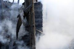 brandkatastrof fördärvar och återstår av ett bränt trähus Bränt bränt till kol vedträ i tjock rök arkivbild