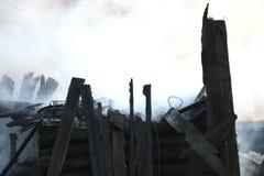 brandkatastrof fördärvar och återstår av ett bränt trähus Bränt bränt till kol vedträ i tjock rök royaltyfri foto