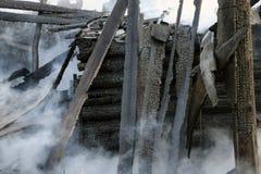 brandkatastrof fördärvar och återstår av ett bränt trähus Bränt bränt till kol vedträ i tjock rök arkivfoton