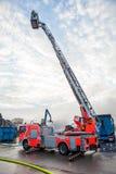 Brandlastbil med en körsbärsröd plockare eller en högstämd bur Arkivfoto