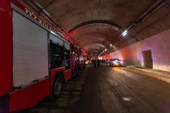 Brandlastbilar som skriver in en stor tunnel med röda ljus för räddningsaktion Royaltyfri Bild