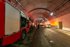 Brandlastbilar som skriver in en stor tunnel med röda ljus för räddningsaktion Arkivfoto