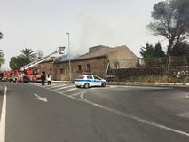 Brandmän är upptagna att släcka en brand i ett gammalt hus Royaltyfri Bild