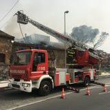 Brandmän är upptagna att släcka en brand i ett gammalt hus Royaltyfria Bilder