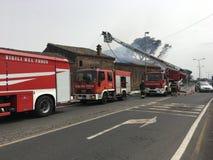 Brandmän är upptagna att släcka en brand i ett gammalt hus Fotografering för Bildbyråer