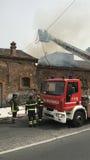 Brandmän är upptagna att släcka en brand i ett gammalt hus Arkivfoton